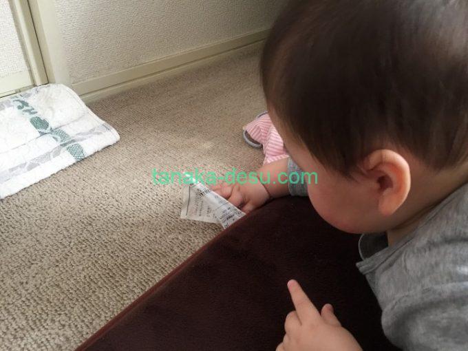 絨毯のタグを触る赤ちゃん