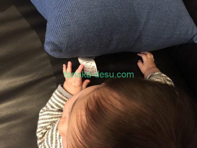 クッションのタグを触る赤ちゃん