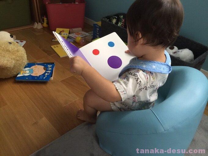 椅子に座って本を読む幼児