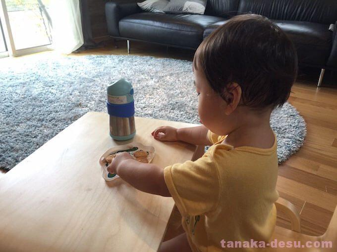 幼児用テーブルでおやつを食べる1歳児