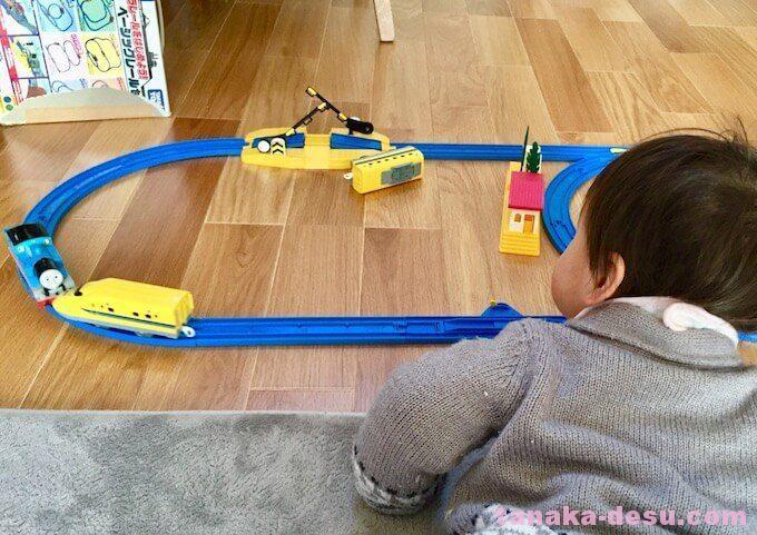 寝ながらプラレールの電車を見る幼児