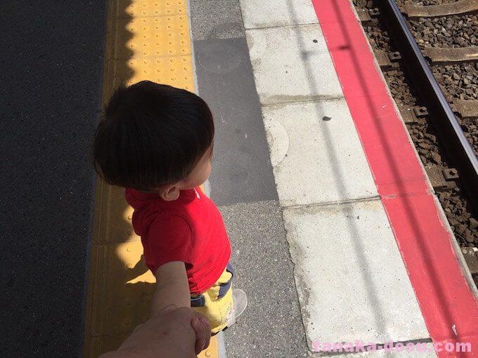駅でママと手を繋ぐ2歳児