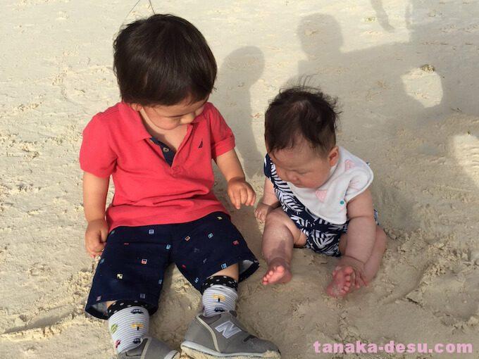 砂の上に座る年子の兄弟